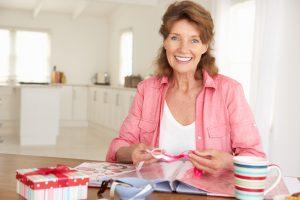 Senior woman scrapbooking at home smiling to camera